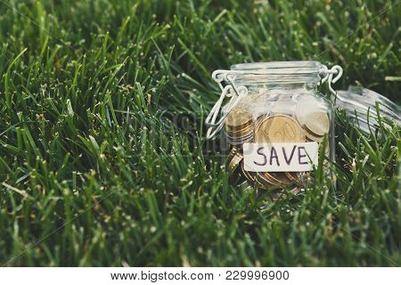 Glass Jar With Coins And Bills On Green Grass Background, Copy Space. Money Box, Saving Money For Dr