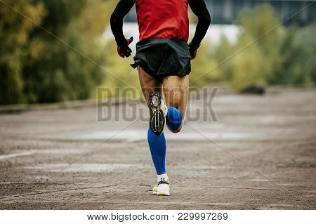 Back Man In Compression Calf Sleeves And Sportswear Running On Road