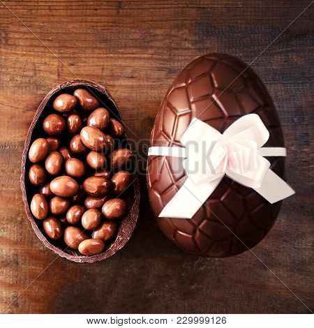 Chocolate Easter Eggs On Wooden Background With Color Ribbon Bow And Broken Egg With Chocolate Candi