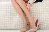 partial view of woman having discomfort while sitting on sofa poster