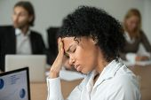 African american businesswoman feeling unwell suffering from headache migraine touching forehead at team meeting, upset black woman employee frustrated by business problem or work stress, head shot poster