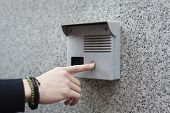Pointing finger of a hand with bracelets pushing the intercom buzzer button on a grey wall. poster