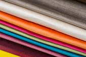 Samples of colorful interior fabrics. Book of fabrics for curtains, upholstery poster