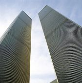 The twin towers of the World Trade Center as viewed from the street. poster