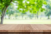Empty wood table over blur green park nature background, tabletop, shelf, counter for product display montage poster