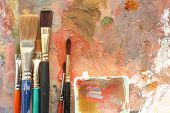 cropped view of used art brushes and mixing bowl against a mixing palette. poster