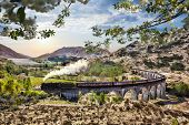 Glenfinnan Railway Viaduct in Scotland with the Jacobite steam train against sunset over lake poster