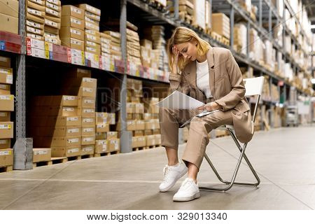 Tired Seriously Business Woman Or Supervisor In A Beige Suit Looks At Documents And Holding Her Fore