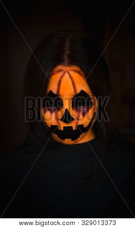 Creepy Halloween Pumpkin Monster Face With Closed Eyes On Black Background. Vertical Portrait Of Sca