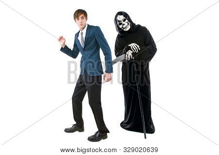 Man In A Halloween Grim Reaper Ghost Costume Chasing, Mocking And Making Fun Of Scared Businessman R