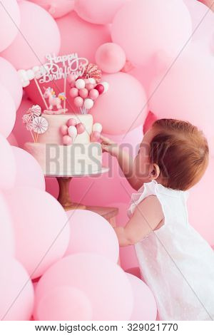 Cute Little Baby Girl Poking Her Finger In Birthday Cake, Decorated With Pastel Pink Balloons On Par