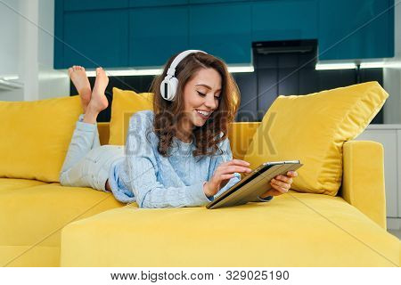 Exuberant Girl Uses Tablet Pc While Laying On The Comfortable Yellow Sofa And Enjoying Nice Melodies