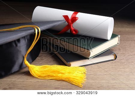 Graduation Hat, Books And Student's Diploma On Wooden Table