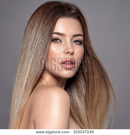 Caucasian woman with long straight hair. Sexy and gorgeous blonde woman. Portrait of an attractive female posing at studio. Closeup face of a beautiful girl with makeup smoky eyes.