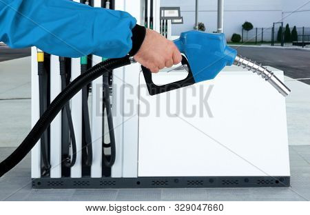 Hand is holding blue gasoline pistol pump fuel nozzle on gas station