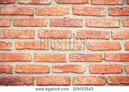 Weathered stained old brick wall background. Brickwork or stonework flooring interior rock old pattern clean concrete grid uneven bricks design stack. Square orange brick wall background. Pattern of red brick wall background. Wall vintage brick texture. poster