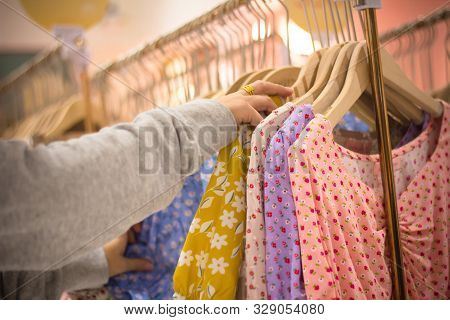 Woman Hand Choosing Clothes Garment In Mall Or Clothing Store. Colorful Dresses On Hangers In A Reta