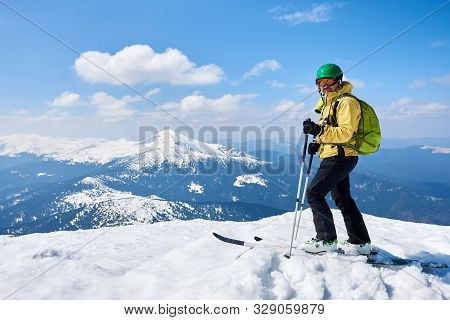 Sportsman Skier In Helmet And Goggles With Backpack Standing On Skis Holding Ski Poles In Deep White