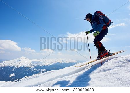 Sportsman Skier In Skiing Equipment With Backpack Jumping In Air Down Steep Snowy Mountain Slope On