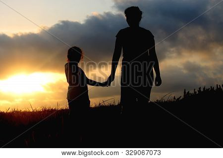 Parenting Concept. Children & Mothers Day Conceptual. With Mom And Daughter Silhouette Holding Hand