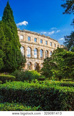 poster of Ancient Roman Arena in Pula, Istria, Croatia, historic amphitheater landscape view through the trees in park