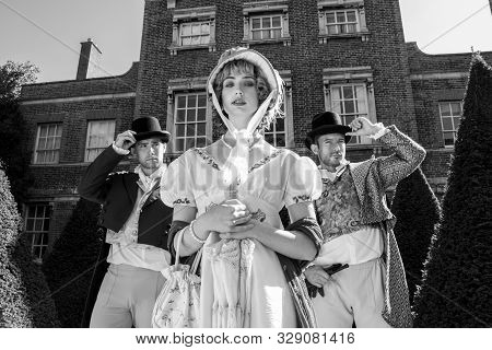 Handsome Trio Of Men And A Woman Dressed In Vintage Clothing, Standing In Front Of Stately Home