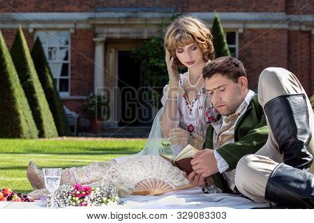 Young Lovers Dressed In Vintage Clothing Sitting On Picnic Blanket. Gentleman Reading To His Lover F