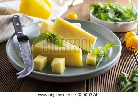 Cheese Plate With Delicous Cheese Slices And A Cheese Knife, Wooden Rustic Table
