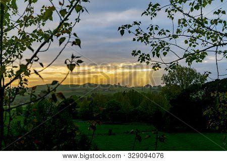 Rising Sun Lights Up Landscape Through Gap In Clouds