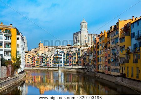 Girona, Spain - January 23, 2019: Colorful And Houses And Bridge Pont De Sant Agusti Reflected In Ri