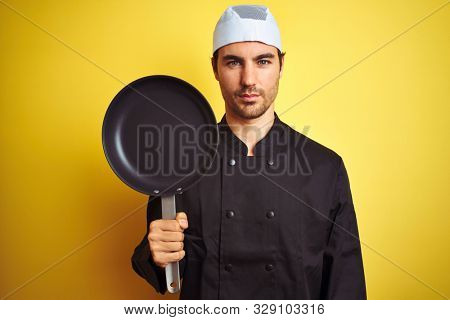 Young chef man wearing uniform and hat holding cook pan over isolated yellow background with a confident expression on smart face thinking serious