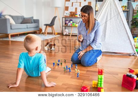 Young caucasian child playing at playschool with teacher. Playing with toy soldiers at playroom around toys.