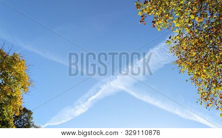 Beautiful Blue Sky With X-shaped Contrails On An Autumn Afternoon