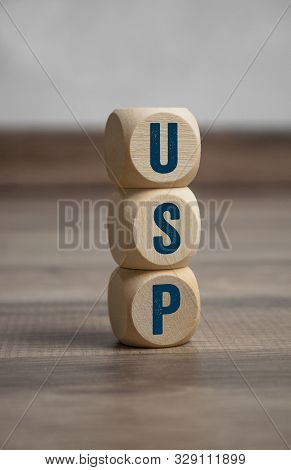 Cubes and dice with acronym USP unique selling proposition or unique selling point on wooden background poster