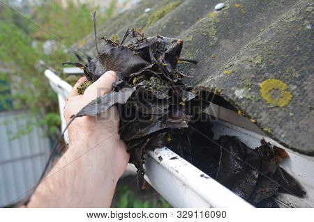 Roofer Cleaning Rain Gutter From Leaves In Spring. Roof Gutter Cleaning Tips. Clean Your Gutters Bef