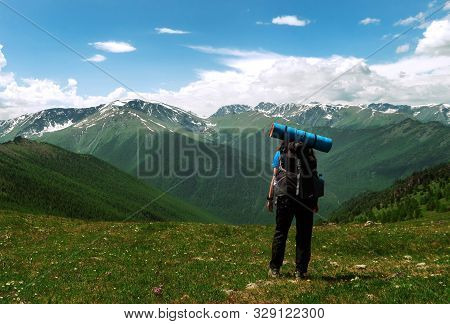 A Young Woman Traveler With A Backpack Looks At The Distance At A Beautiful Mountain Range.