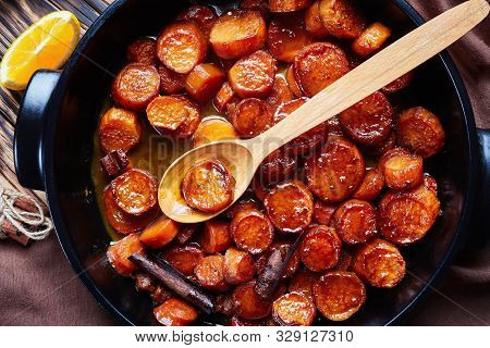Candied Yams, Sweet Potatoes Cooked With Orange Juice, Cinnamon, Brown Sugar And Butter In A Black C