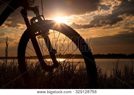 Bicycle Wheel On A Sunset Background. Bicycle On The Background Of A Summer Evening Landscape. Silho