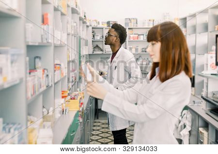 Two Young Multiethnical Pharmacists Working At Modern Pharmacy. Female Pharmacist Holding Package Wi