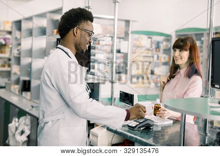 Pretty Young Caucasian Woman Paying For Mediciens With Credit Card In Pharmacy. African Man Pharmaci