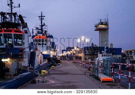Evening At The Seaport - Sleeping Tugs At The Port Quay Against The Backdrop Of A 24-hour Watchful S