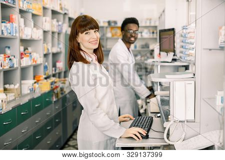 Two Young Cheerful Pharmacists African Man And Caucasian Woman Working Together And Using Computers.