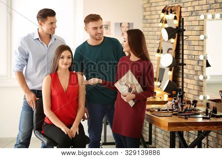 Professional makeup artist teaching trainees in salon. Apprenticeship concept