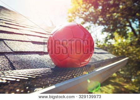 Red soccer ball stuck on gutter mesh on a roof poster