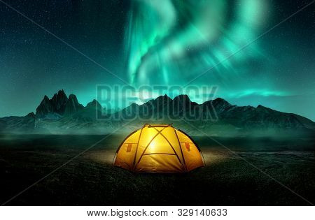 A Glowing Yellow Camping Tent Under A Beautiful Green Northern Lights Aurora. Travel Adventure Lands