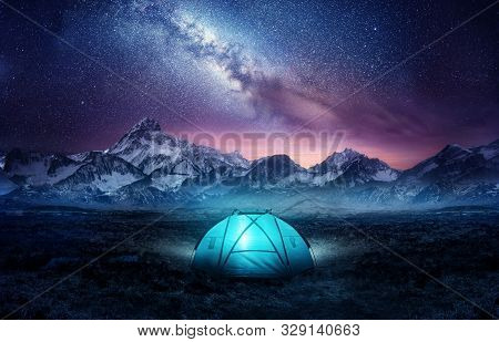 Camping In The Mountains Under The Stars. A Tent Pitched Up And Glowing Under The Milky Way. Photo C