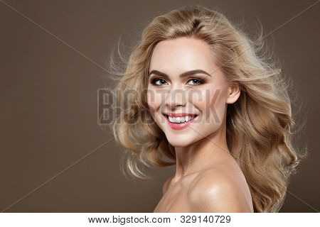Excitement Blonde Haired Woman Portrait With Blue Eyes And Healthy Long Shiny Wavy Hairstyle. Volume
