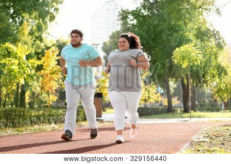 Overweight Couple Running Together In Park, Weightloss