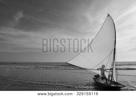 Icapui, Ceara, Brazil - June 01, 2016: Silhouette Of Young Fisherman Behind The Raft Sail, On The Sh