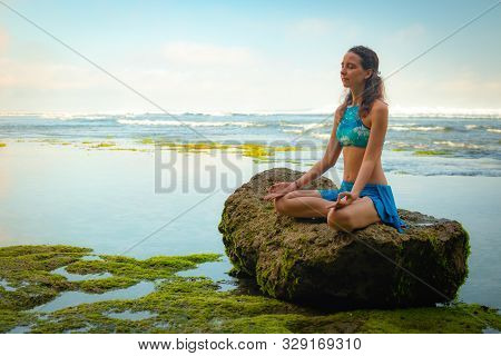 Young Woman Seating On The Rock, Meditating, Practicing Yoga And Pranayama At The Beach, Bali. Hands